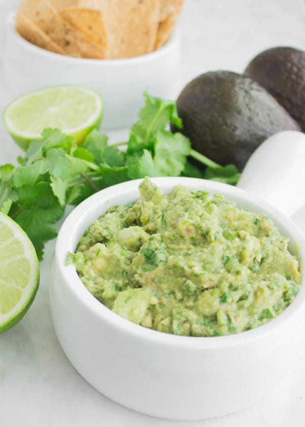 Side view of Classic Mexican Guacamole served in a white bowl with some nacho chips, lime, avocados and cilantro in the background
