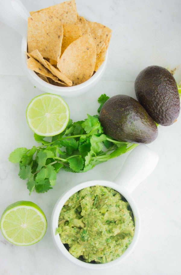 Overhead shot of Classic Mexican Guacamole served in a white bowl with some nacho chips, lime, avocados and cilantro in the background