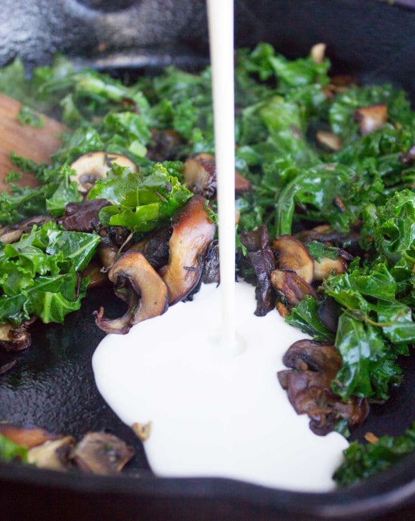 cream being poured into a skillet with fried kale and mushrooms