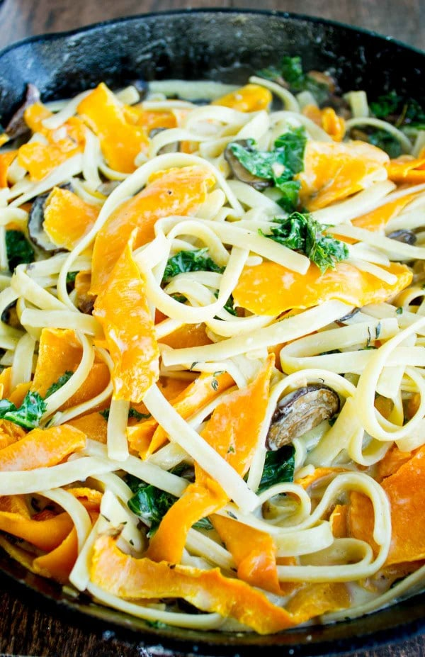 Overhead shot of Healthy Kale Squash Mushroom Pasta in a creamy sauce served in a black skillet