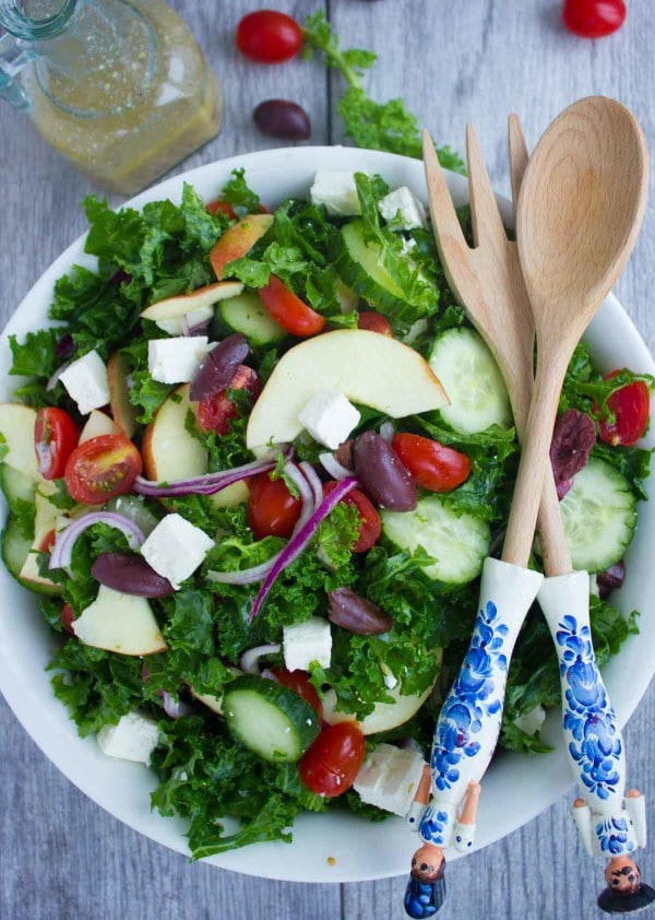 Healthy Kale Greek Salad served in a big white salad bowl with wooden salad spoons on the side