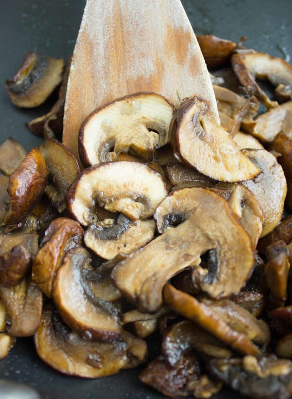 sliced cremini mushrooms frying in a black skillet