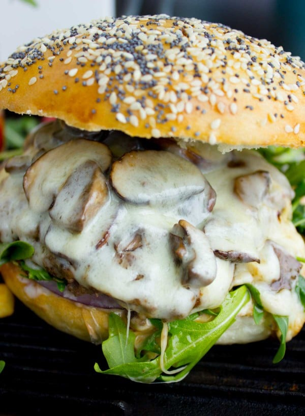 side view of a Mushroom Swiss Burger with plenty of Swiss cheese covering patty and mushrooms
