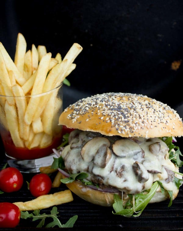 side view of a Mushroom Swiss Burger with cocktail tomatoes and fries on the side