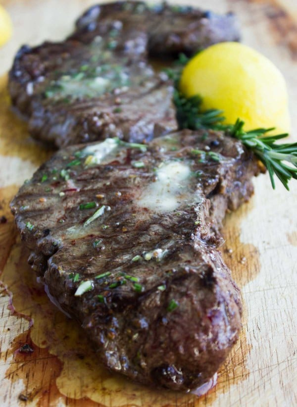 Grilled Steaks with Rosemary Lemon Butter on a wooden chopping board with a lemon and some fresh rosemary in the background