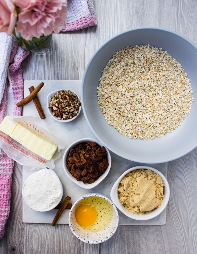 Ingredients for healthy oatmeal cookies: a bowl of oats, bowl of flour, butter, sugars, nuts, raisin, egg and cinnamon