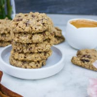 a plate stacked with healthy oatmeal cookies, an expresso cup and cinnamon sticks on a white marble