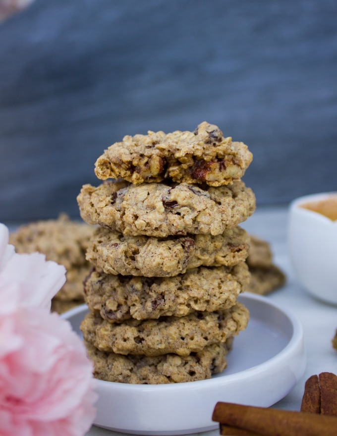 stacks of healthy oatmeal cookies wwith one bitten cookie on the top showing the texture of the cookies on the inside