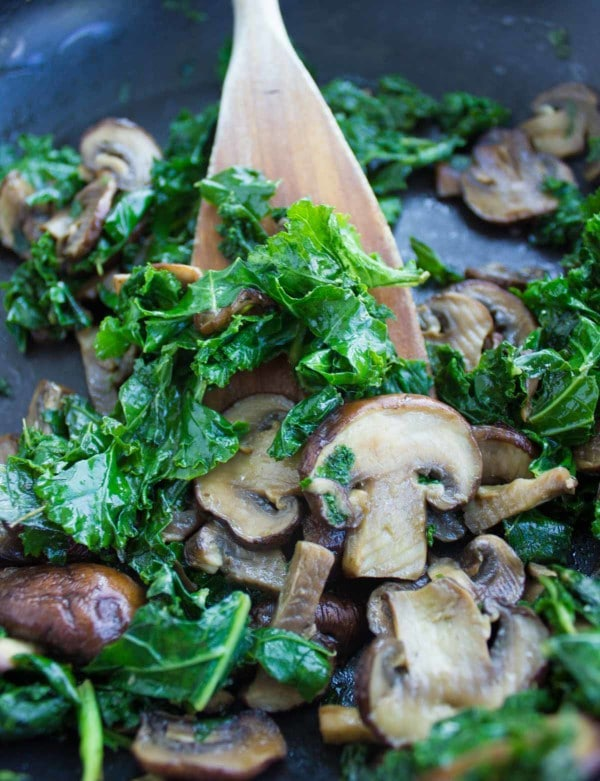 kale and mushrooms being sauteed in a black skillet