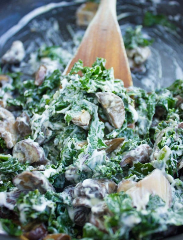 cream cheese being stirred into a skillet with sauteed kale and mushrooms