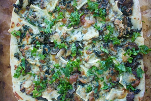 overhead shot of Kale Mushroom Brie Pizza fresh out of the oven on a wooden tabletop