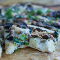 a wedge of Kale Mushroom Brie Pizza with a bite taken out the front
