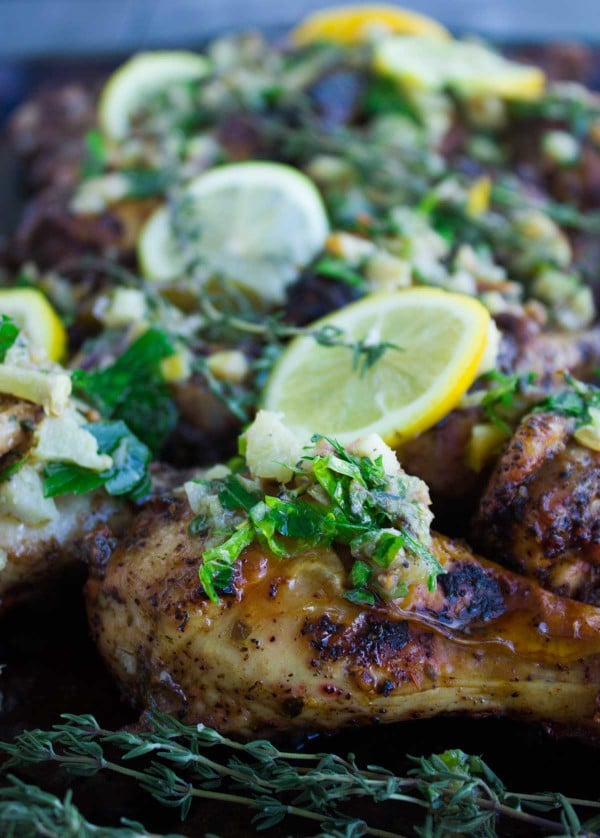 Lemon Artichoke Garlic Roast Chicken with Salsa on a tray, covered with lemon slices and fresh thyme