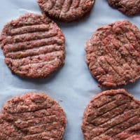 Shaped burger patties on a parchment paper ready to be cooked