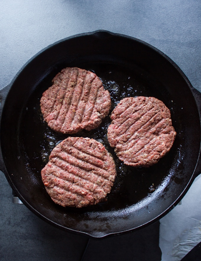 Three burgers on a skillet cooking