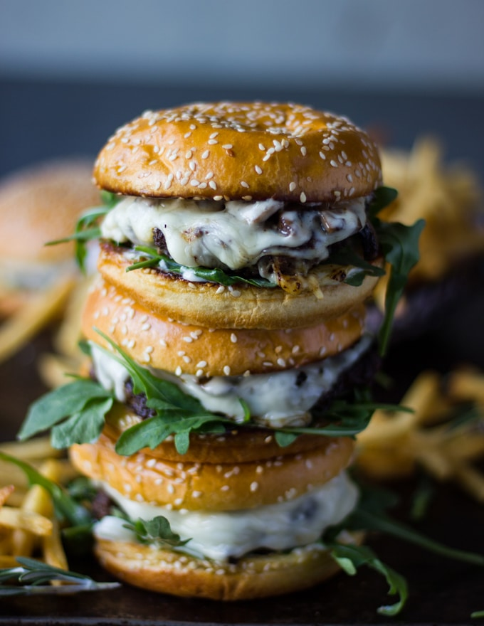 A stack of three mushroom swiss burgers surrounded by french fries