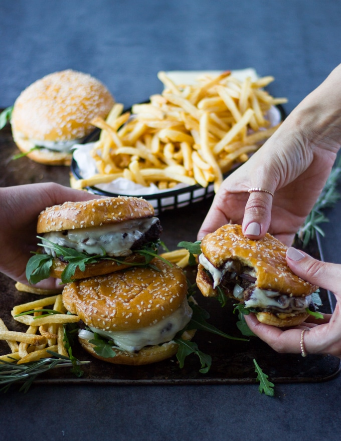 Family hands each picking up a mushroom swiss burger and fries to enjoy the burger meal