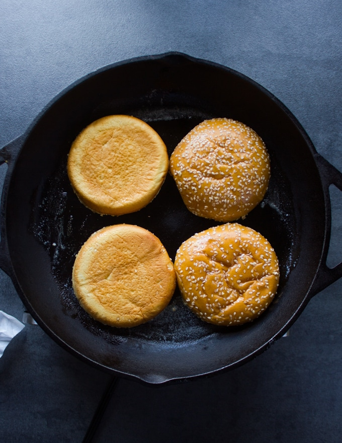 A skillet with brioche buns placed cut side down for toasting