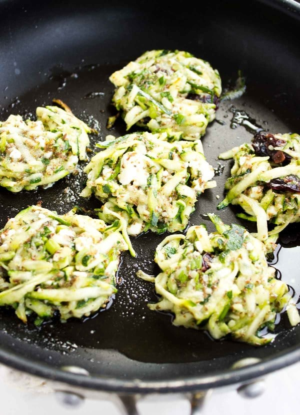 gluten-free zucchini fritters with feta and cranberries being fried in a pan