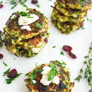 Zucchini Feta Cranberry Fritters served on a white tabletop sprinkled with chopped herbs and cranberries