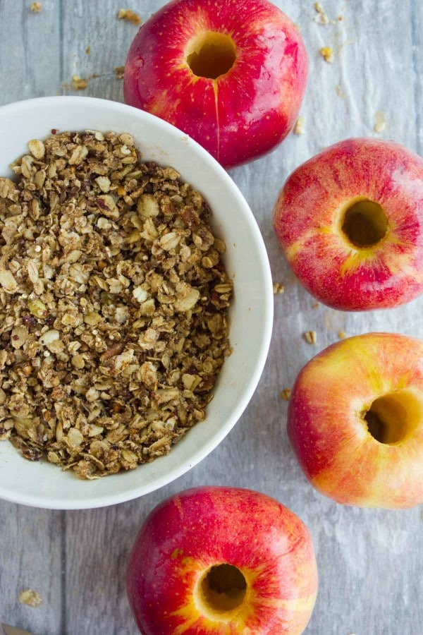 a bowl of granola with whole cored apples on the side