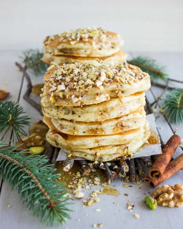 a stack of Baklava Pancakes topped with chopped nuts and drizzled with Maple Syrup