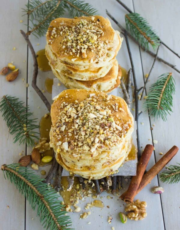 two stacks of Baklava Pancakes with Maple Syrup surrounded by cinnamon sticks and spruce twigs