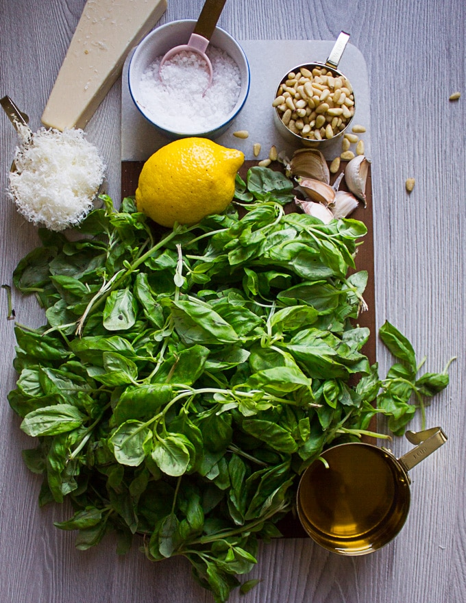 Ingredients for basil pesto over a wooden board such as fresh basil leaves, garlic, lemon, pine nuts, parmesan cheese salt and olive oil