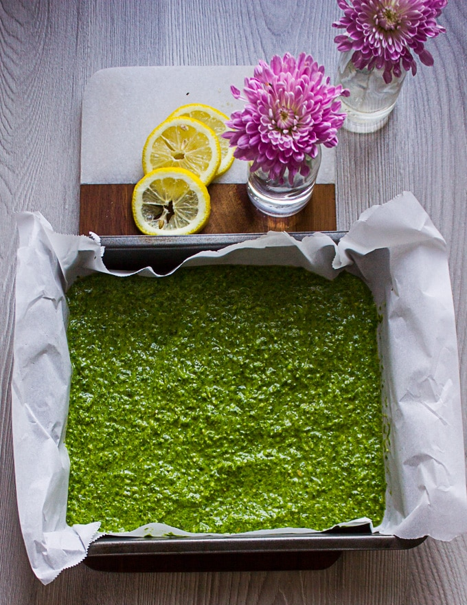 A batch of basil pesto spread over parchment paper in a baking pan and ready to go in the freezer surrounded by lemon slices