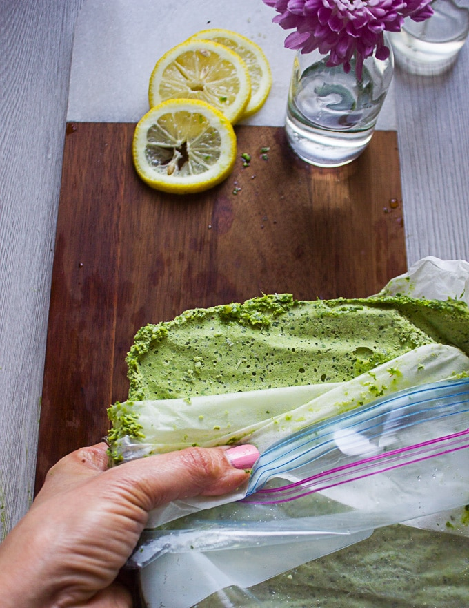 A hand holding the opened bag of frozen pesto showing the texture