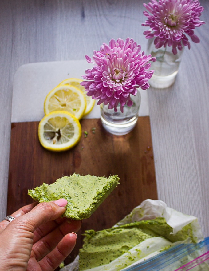 A hand holding a chunk of frozen basil pesto ready to use