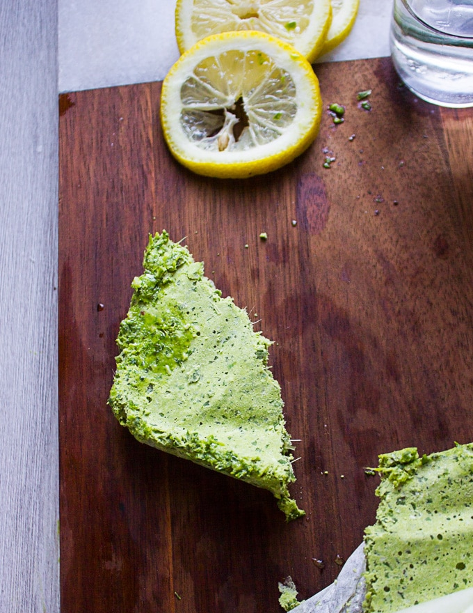 A chunk of frozen basil pesto on a wooden board surrounded by a slice of lemon