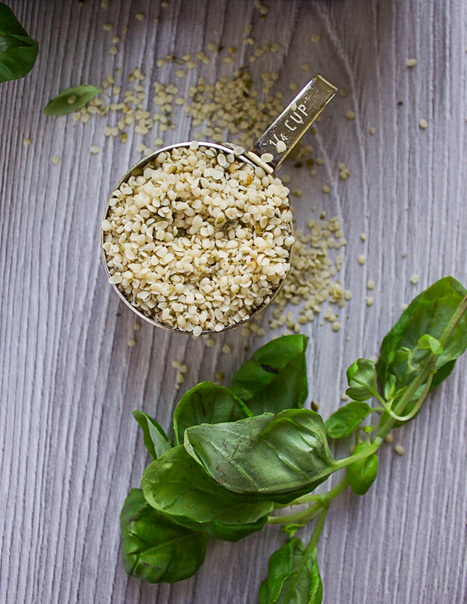 A cup of hemp seeds showing the texture and look of hemp surrounded by fresh basil leaves