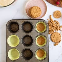 A muffin pan lined with baking sheets and a cookie pressed at the bottom of each paper to make the cheesecake base