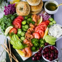A fully arranged platter with the bagels, veggies, fruits, the sauces and ready to eat