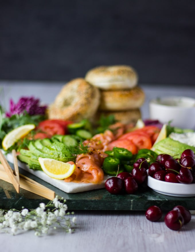 Side view of the assembled smoked salmon platter showing the fruits and avocados in focus and bagels in the background