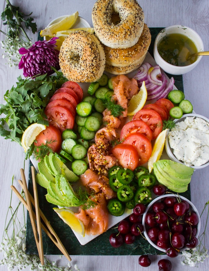 Chopped up and arranged smoked salmon platter on a marble board with sliced tomatoes, cucumbers, avocados, fruits, arugula, dill mustard sauce, herbed cream cheese, bagels.