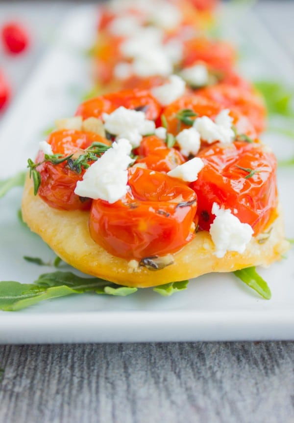 Mini Tomato Tartes Tatin sprinkled with crumbled feta cheese lined up on a while rectangular plate