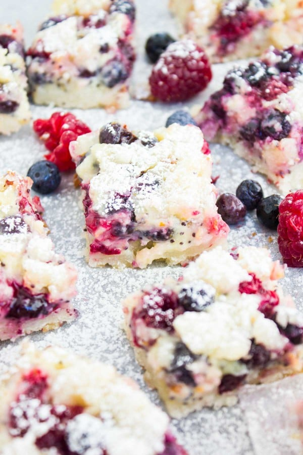 Close-up of sugar-dusted Berry Citrus Poppy Seed Bars with some mixed berries scattered in between