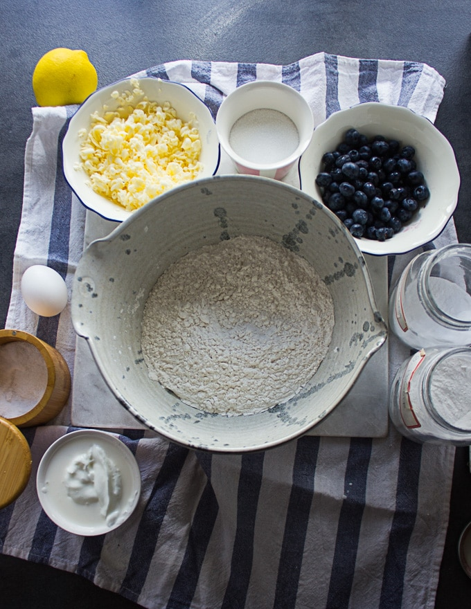 Ingredients for drop biscuits, a bowl of flour, some baking powder, an egg, grated butter, fresh blueberries, lemon, sour cream in a bowl