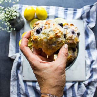 A hand holding a glazed drop biscuits with blueberries and lemon over a plate of drop biscuits