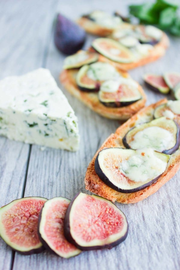 Fig Blue Cheese Honey Crostini drizzled with honey, served on a rustic table with a wedge of blue cheese and some figs in the background