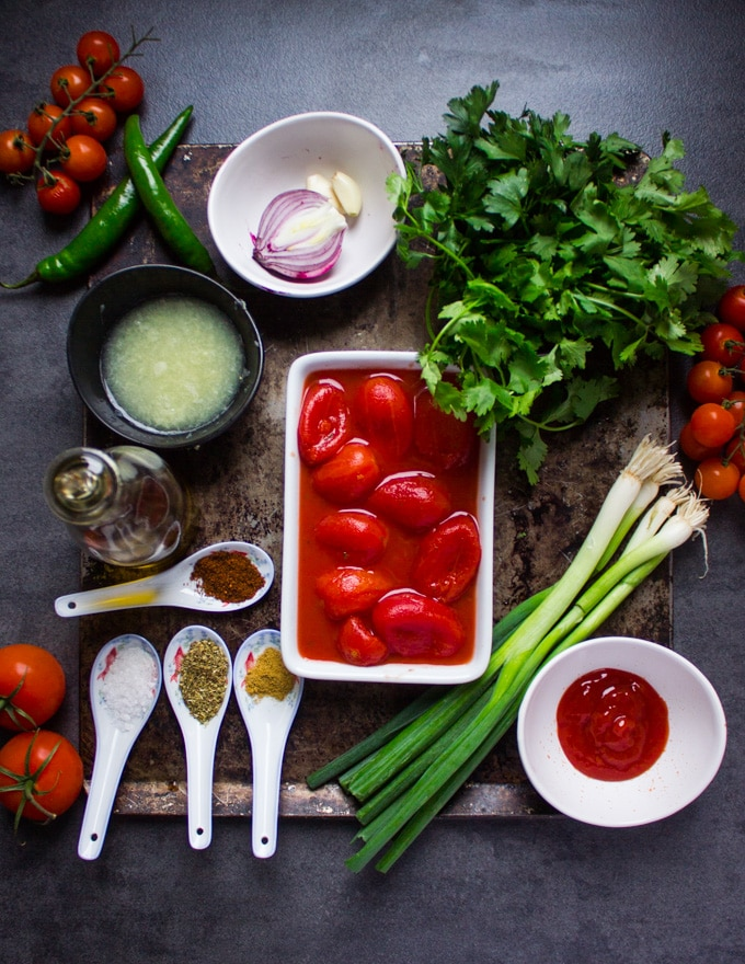 ingredients of homemade salsa on a board. a bowl of tomatoes, scallions, lime juice in a bowl, seasoning in small spoons, scallions, fresh parsley and cilantro, onions, garlic, ketchup and jalapeno