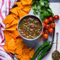 a metal bowl of salsa surrounded by chips, fresh tomatoes, jalapeno and cilantro over a tray