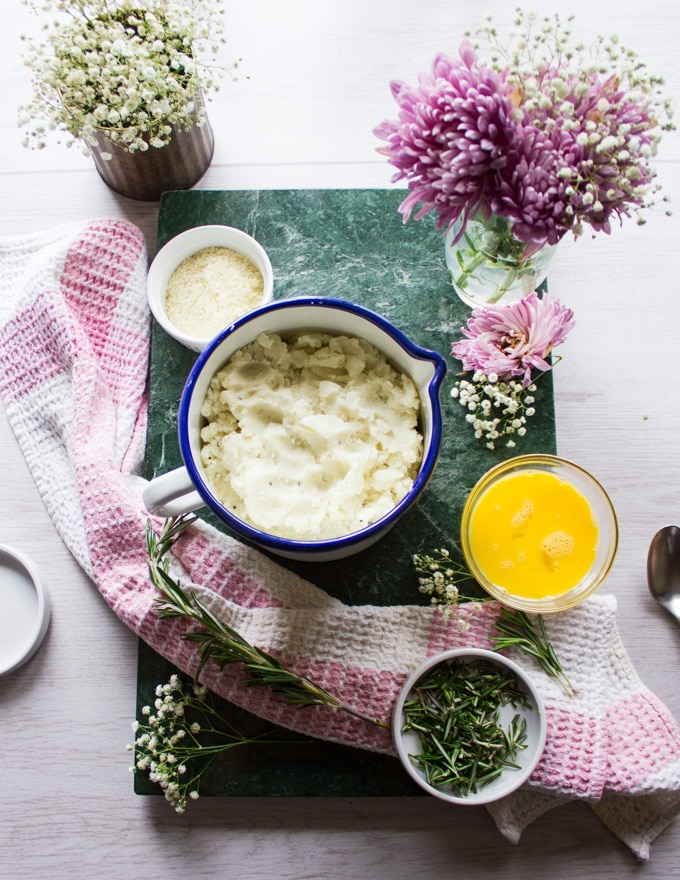 Ingredients for the potato pancakes, a bowl of leftover mashed potatoes, an egg in a bowl, fresh rosemary in a bowl, grated parmesan cheese in a bowl surrounded by fresh flowers