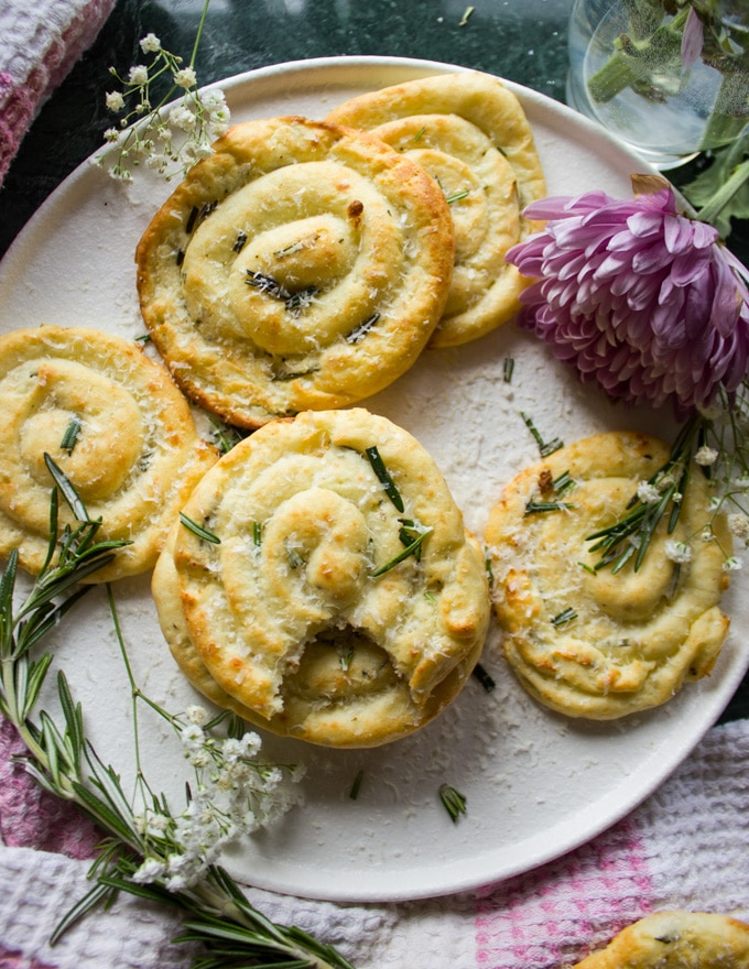 A plate with mashed potato pancakes with a fresh sprig of rosemary and flowers