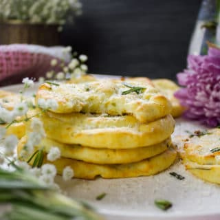 stacks of potato pancakes on a plate with a top bitten pancake showing the inside fluffy mashed potato texture