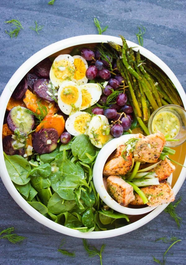 Salmon Asparagus Sweet Potato Nicoise Salad arranged in a big salad bowl and topped with sweet potatoes grapes, boiled eggs and broiled salmon and asparagus