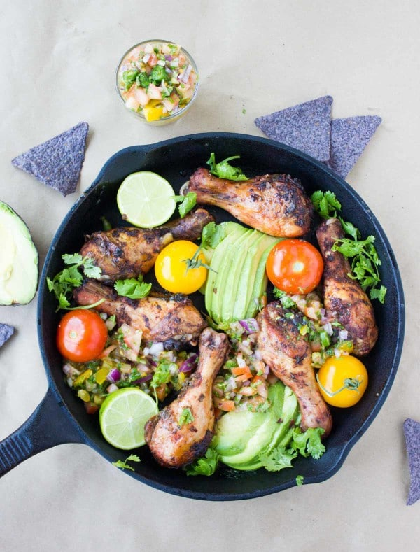 overhead shot of Salsa Avocado Roast Chicken Skillet served in a black skillet with purple corn chips surrounding it
