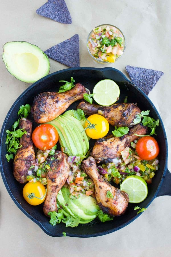 overhead shot of Mexican Salsa Avocado Roast Chicken Skillet served in a black skillet with purple corn chips and halved avocados surrounding it